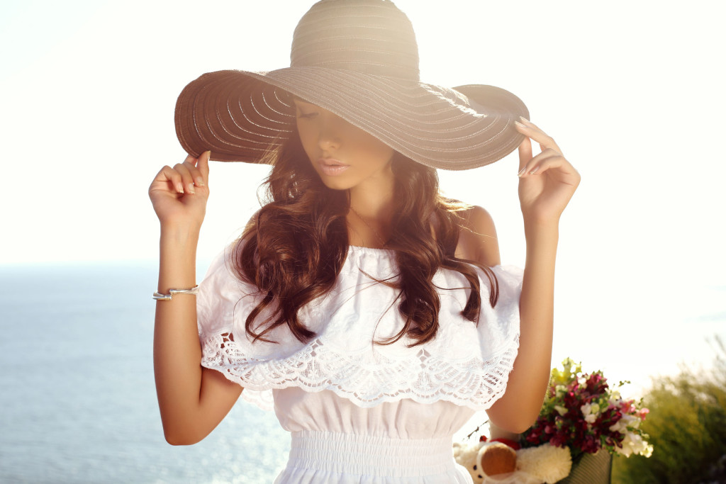 48829706 - fashion outdoor photo of beautiful sensual girl with dark hair in elegant dress and hat riding by summer beach